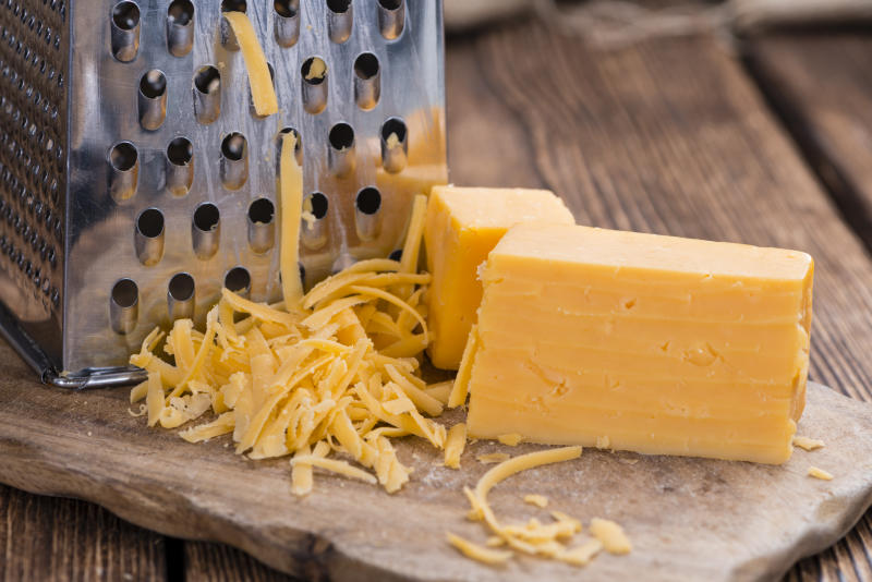 A photo of Grated Cheddar Cheese on rustic wooden background
