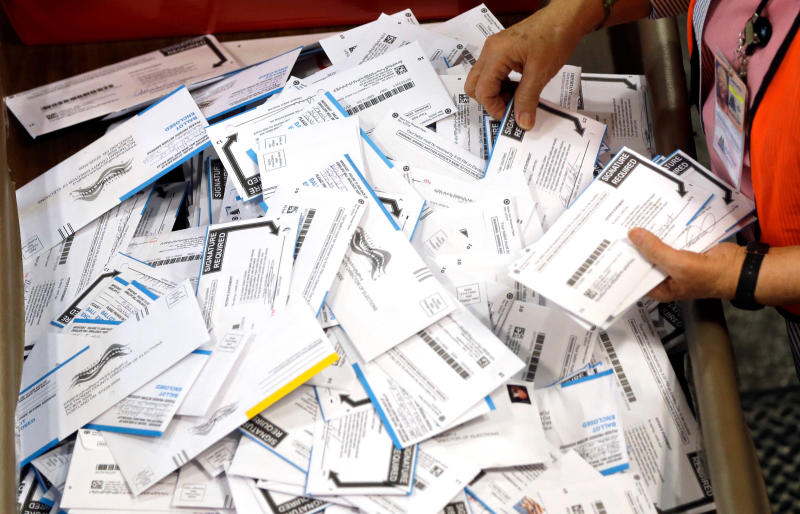 FILE - In this May 17, 2016, file photo, ballots are prepared for counting at Multnomah County election headquarters in Portland, Ore. The coronavirus has knocked presidential primaries back several weeks as officials worry about voters crowding into polling places. If the disease remains a hazard in November, Democrats say there's only one solution to preserve the November election, national voting by mail. (AP Photo/Don Ryan, File)