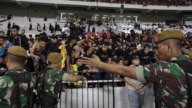 TNI mengevakuasi suporter Malaysia karena serangan dari suporter Timnas Indonesia saat laga Kualifikasi Piala Dunia 2022 di SUGBK, Jakarta, Kamis (5/9). (Bola.com/Vitalis Yogi Trisna)