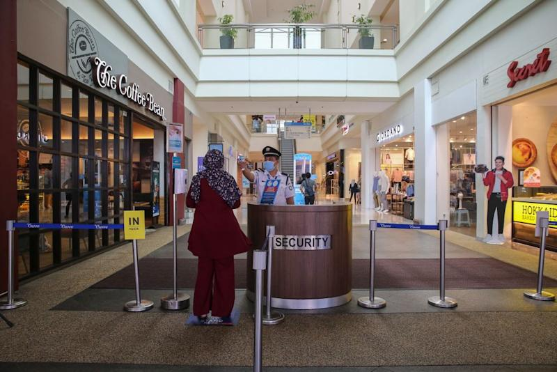 A security personnel checks a patron's temperature at The Curve shopping mall entrance in Petaling Jaya May 28, 2020. — Picture by Yusof Mat Isa