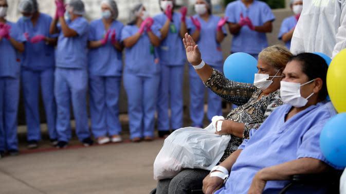 Petugas medis merayakan bersama Helena Elvira, 63, (kanan) dan Alzira Neves, 53, setelah keluar dari rumah sakit lapangan di Stadion Nasional Mane Garrincha di Brasilia, Brasil, Kamis (15/10/2020). Tiga pasien COVID-19 terakhir itu dipulangkan setelah dinyatakan sembuh. (AP Photo/Eraldo Peres)