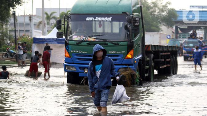 Warga berjalan melintasi genangan banjir rob yang menggenangi kawasan Pelabuhan Nizam Zachman, Muara Baru, Jakarta, Jumat (5/6/2020). Banjir rob di Pelabuhan Muara Baru tersebut terjadi akibat cuaca ekstrem serta pasang air laut. (Liputan6.com/Helmi Fithriansyah)