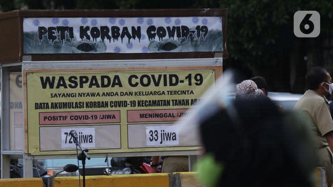Warga melintasi tanda peringatan bahaya COVID-19 di sekitar Pasar Blok A Tanah Abang, Jakarta, Selasa (1/9/2020). Guna meningkatkan kewaspadaan masyarakat, muspida kecamatan Tanah Abang memajang peti mati dilengkapi data jumlah korban COVID-19 di wilayah tersebut. (Liputan6.comHelmi Fithriansyah)