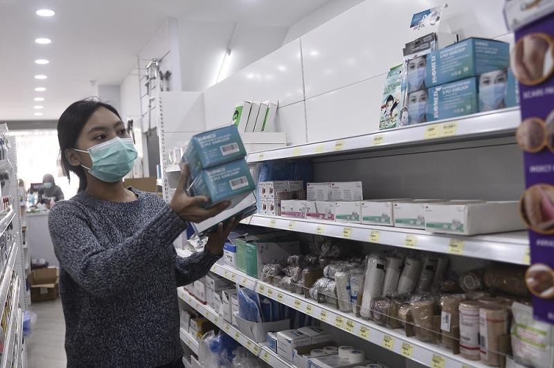 A sales assistant arranges boxes of face masks at a Pharmhouse Pharmacy outlet in Setia Alam on January 28, 2020. — Picture by Miera Zulyana