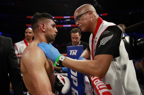 Virgil Hunter consoles Khan after the fight is waved off (Reuters)