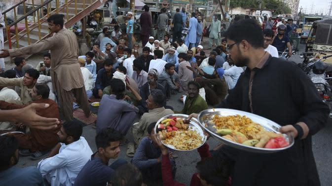 Relawan mendistribusikan makanan untuk warga saat berbuka puasa bersama selama bulan suci Ramadan di Karachi, Pakistan, Selasa (12/5/2020). Warga berbuka puasa bersama setelah pemerintah melonggarkan lockdown terkait pandemi virus corona COVID-19. (AP Photo/Fareed Khan)