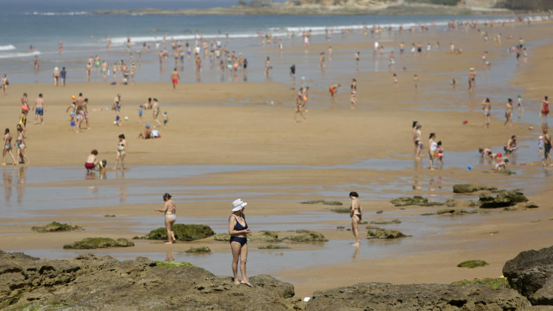 People walk along the water at the Carcavelos beach, outside Lisbon, Tuesday, May 26, 2020. As the government eases the coronavirus lockdown rules, people have been allowed back on the beaches with recommendations to keep social distance. Portugal is experience temperatures above average, reaching 30C in Lisbon. (AP Photo/Armando Franca)