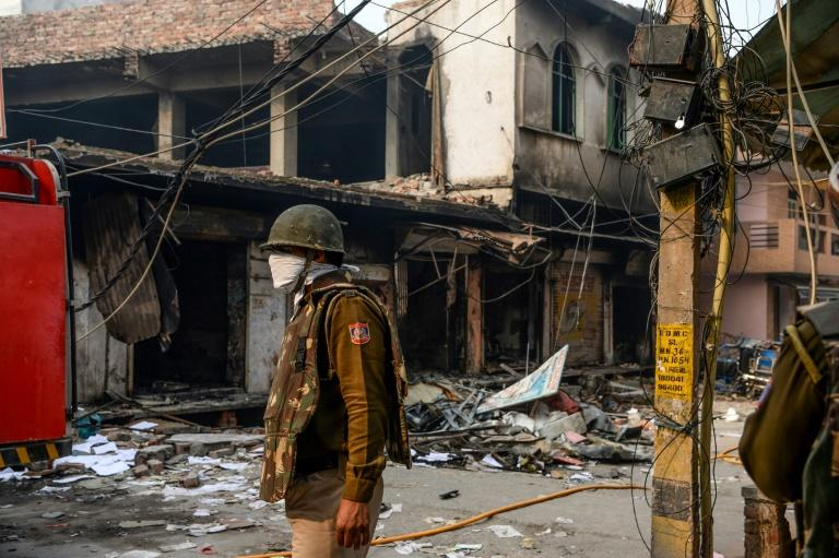 A security personnel stands guard on a street near burnt-out premises on February 26 following clashes in New Delhi