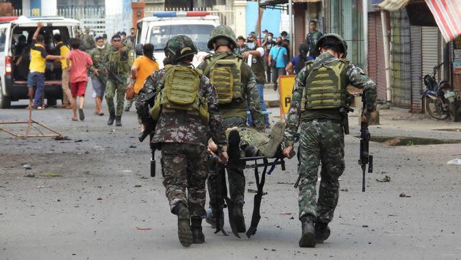Sejumlah tentara membawa rekannya usai bom rakitan meledak dekat kendaraan militer di Kota Jolo, Pulau Sulu, Filipina, Senin (24/8/2020). Sebanyak 10 orang tewas dan puluhan lainnya terluka -banyak dari mereka tentara atau polisi- dalam pemboman ganda tersebut. (Nickee BUTLANGAN/AFP)