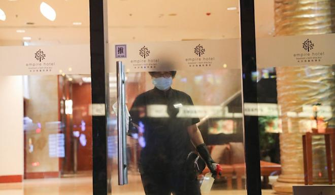 A staff member cleans the lobby doors at the Empire Hotel. Photo: Sam Tsang