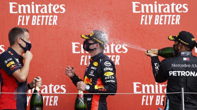 Pembalap Mercedes Lewis Hamilton (kanan) menyemprotkan sampanye ke pembalap Red Bull Max Verstappen yang memenangkan 70th Anniversary Formula 1 Grand Prix di Sirkuit Silverstone, Silverstone, Inggris, Minggu (9/8/2020). Max Verstappen tercepat di F1 GP Silverstone 2020. (Andrew Boyers, Pool via AP)