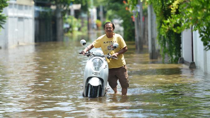 Seorang pria mendorong sepeda motor di sebuah jalan yang terendam banjir pascahujan lebat di Bangkok, Thailand (31/8/2020). (Xinhua/Rachen Sageamsak)