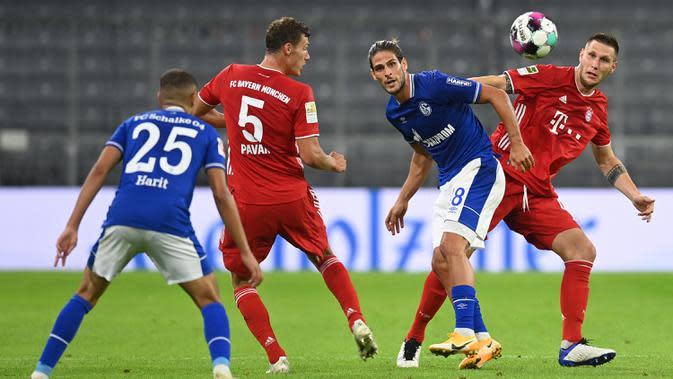 Bek Bayern Munchen, Benjamin Pavard, berebut bola dengan pemain Schalke pada laga Liga Jerman di Allianz Arena, Sabtu (19/9/2020) dini hari WIB. Bayern Munchen menang 8-0 atas Schalke. (AFP/Christof Stache)