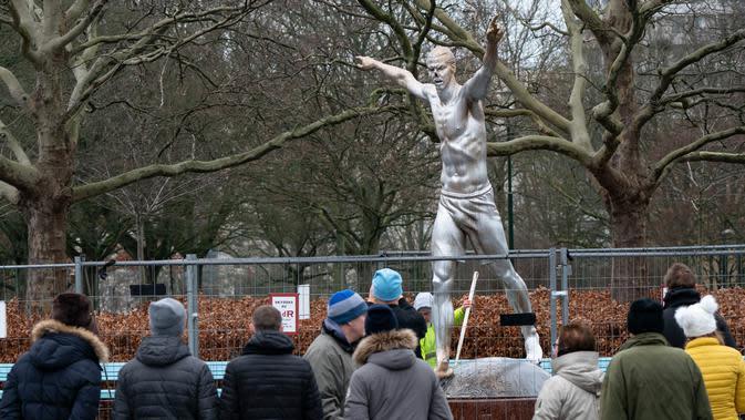 Warga menyaksikan patung Zlatan Ibrahimovic yang rusak, Malmo, Swedia, Minggu (22/12/2019). Perusakan patung yang terjadi untuk kesekian kali tersebut dilakukan fans Malmo karena kecewa sang idola membeli saham di klub rival, Hammarby. (Johan Nilsson/TT News Agency via AP)
