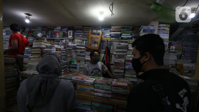 Pedagang buku melayani pembeli di Kwitang, Senen, Jakarta, Minggu (27/9/2020). Menurut keterangan para pedagang, penjualan buku di masa pandemi menurun hingga 50 persen dikarenakan masyarakat saat ini sudah beralih melakukan transaksi pembelian secara daring. (Liputan6.com/Angga Yuniar)