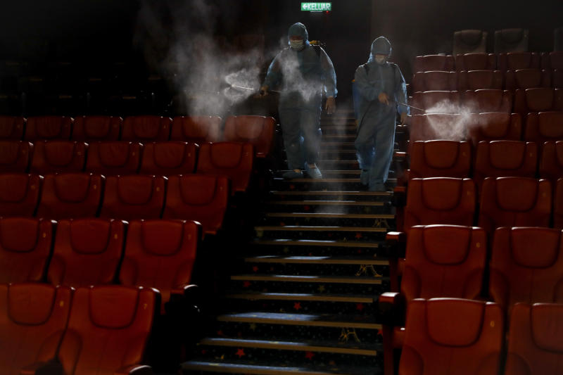 Cinema staff spray disinfectant in a theater to prepare for reopening on July 1 in Kuala Lumpur, Malaysia, on Friday, June 26, 2020. Malaysia entered the Recovery Movement Control Order (RMCO) after three months of coronavirus restrictions. (AP Photo/Vincent Thian)