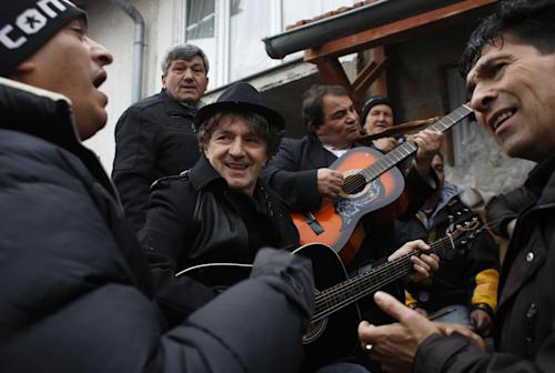 Bosnia's most popular former rock star, now a composer of ethnic music inspired by Roma culture, Goran Bregovic, plays guitar surrounded by Bosnian Roma people in Sarajevo, on Tuesday, Dec. 10, 2013. Bosnia's most popular musician is searching for talented Roma children to help them get an education in music. On Tuesday, 63-year-old former rock star Goran Bregovic visited Sarajevo's biggest Roma settlement of Gorica. That's the same name he has given his new foundation, which will provide scholarships to Roma kids who wish to study music but can't afford to. (AP Photo/Amel Emric)