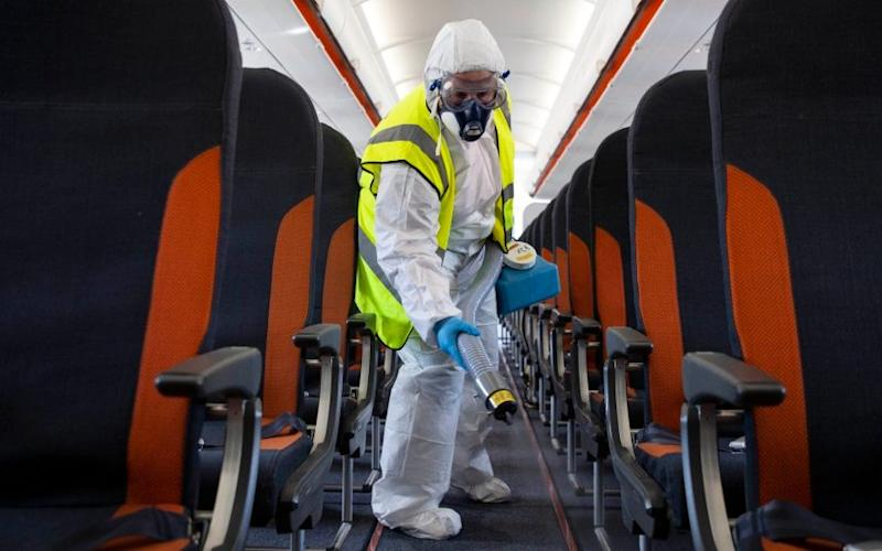 Deep clean: A member of easyJet staff wears protective clothing to decontaminate an aircraft - part of measures to prevent a second wave of coronavirus - MATT ALEXANDER/PA