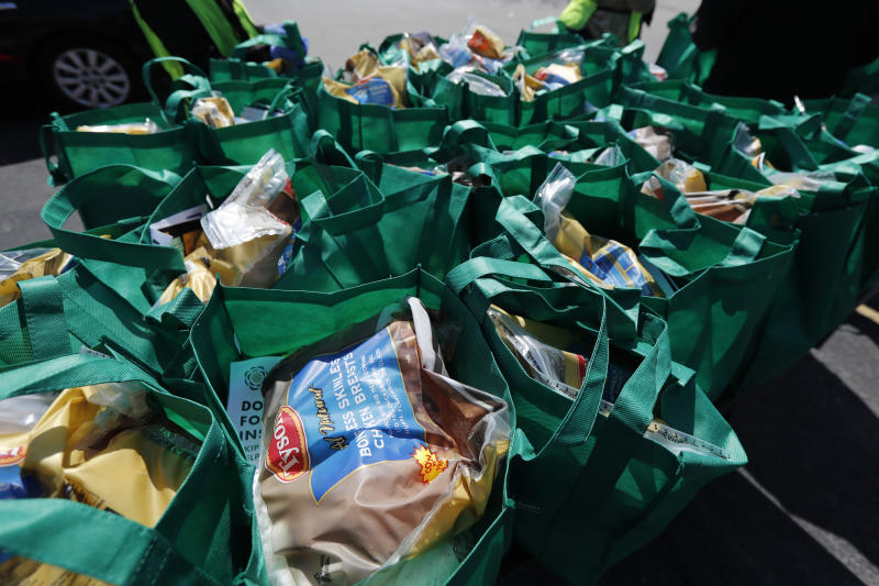In this Tuesday, May 12, 2020, photo, bags of fresh food wait to be given away at an event sponsored by the Greater Chicago Food Depository in the Auburn Gresham neighborhood of Chicago. Across the country, food insecurity is adding to the anxiety of millions of people, according to a new survey that finds 37 percent of unemployed Americans ran out of food in the past month, while 46 percent worried that they would. The nationwide unemployment rate on Friday was 14.7 percent, the highest since the Great Depression.(AP Photo/Charles Rex Arbogast)