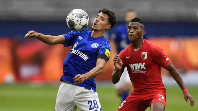 Pemain Augsburg, Carlos Gruezo, berebut bola dengan Schalke 04, Alessandro Schoepf, pada laga Bundesliga di Veltins-Arena, Minggu (24/5/2020). Augsburg menang dengan skor 3-0 atas Schalke 04. (AP/Martin Meissner)