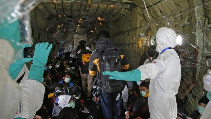 Sejumlah WNI yang dievakuasi dari Wuhan, China berada di dalam pesawat Hercules sebelum menuju Natuna, Kepulauan Riau di bandara internasional Hang Nadim, Batam, Minggu (2/2/2020). (Photo by Handout/Indonesian Embassy/AFP)