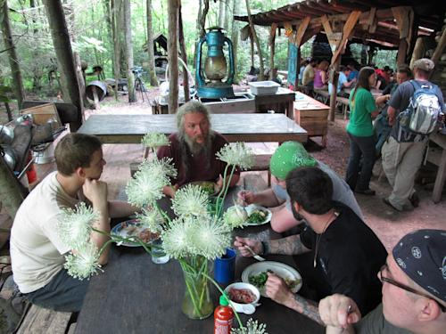 Naturalist Eustace Conway, center, speaks to diners at the Nacho Mama's eating hall at Turtle Island Preserve in Triplett, N.C., on Thursday, June 27, 2013. People come from all over the world to learn natural living and how to go off-grid, but local officials ordered the place closed over health and safety concerns. (AP Photo/Allen Breed)