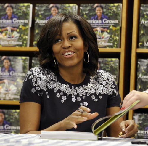 "FILE - In this May 7, 2013 file photo, First lady Michelle Obama signs copies of her book ""American Grown: The Story of the White House Kitchen Garden and Garden Across America"" at the Politics & Prose bookstore in Washington. The nation's first lady turns 50 on Friday and, by her own account, feels more relaxed now that President Barack Obama's days as a candidate for elected office are over. (AP Photo/Susan Walsh)"