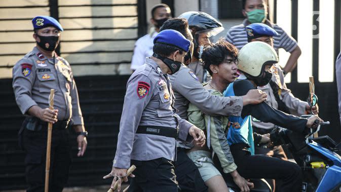 Polisi membawa seorang pria saat terjadi bentrok di kawasan Pejompongan, Jakarta, Rabu (7/10/2020). Belum bisa dipastikan apakah aksi tersebut berkaitan dengan isu aksi penolakan pengesahan UU Omnibus Law Cipta Kerja. (Liputan6.com/Faizal Fanani)