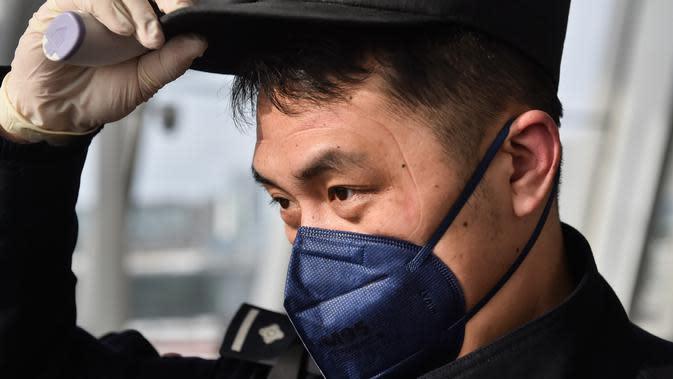 Wu Shengzao, seorang personel kepolisian, mencopot kacamata pelindung usai memeriksa kondisi seorang penumpang di Bandara Internasional Daxing di Beijing, ibu kota China, pada 1 Februari 2020. (Xinhua/Peng Ziyang)