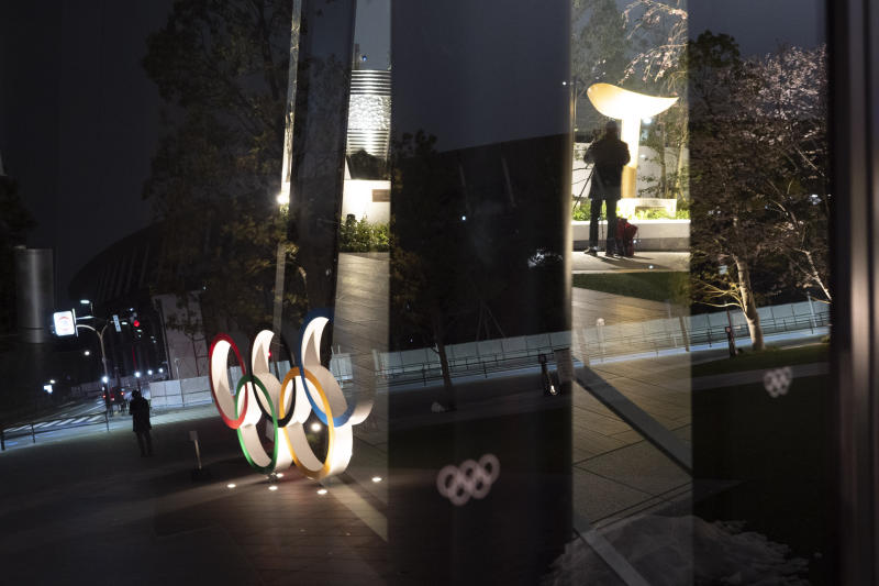 The Olympic rings are reflected on the facade of Japan Olympic Museum Monday, March 30, 2020, in Tokyo. The Tokyo Olympics will open next year in the same time slot scheduled for this year's games. Tokyo organizers said Monday the opening ceremony will take place on July 23, 2021. (AP Photo/Jae C. Hong)