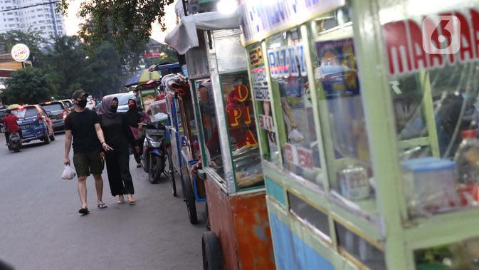 Warga melintasi deretan penjual makanan berbuka puasa di kawasan Bendungan Hilir, Jakarta, Sabtu (25/4/2020). Meski ditengah pandemi virus Covid-19, masyarakat masih antusias berburu penganan berbuka puasa dengan tetap menerapkan pola jaga jarak dan memakai masker. (Liputan6.com/Helmi Fithriansyah)