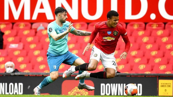 Pemain Manchester United, Mason Greenwood, berebut bola dengan pemain Diego Rico pada laga Premier League di Stadion Old Trafford Sabtu (4/6/2020). Manchester United menang 5-2 atas Bournemouth. (AP/Peter Powell)