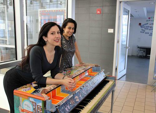 In this 2011 photo provided by Sing for Hope, Sing for Hope Co-Founding Directors Camille Zamora, left, and Monica Yunus lean on a piano decorated by artist Jillian Logue, after it found its final home in Betances Community Center in the Bronx borough of New York. A festival featuring 88 pianos planted all around New York City's streets and parks is returning this summer. It's called Sing for Hope Pianos and will run from June 1, 2013 through June 16. Each of the pianos will be painted and decorated by different artists.(AP Photo/Sing for Hope, Lekha Singh)
