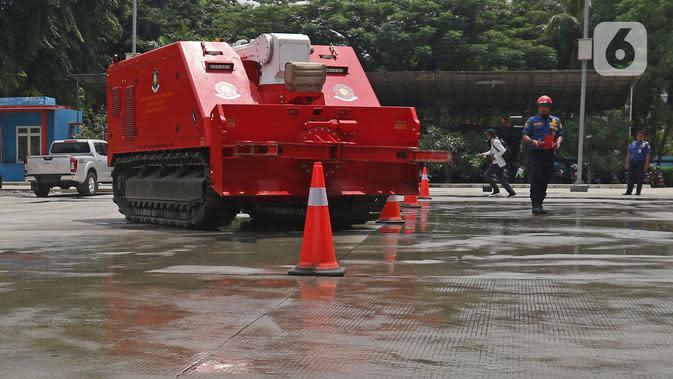 Petugas pemadam kebakaran mengoperasikan robot damkar jenis Dok-INK MVF- U3 di kantor PKP DKI Jakarta, Kamis (13/2/2020). Robot yang besarnya berkisar 3x4 meter dan digerakkan dengan remote control ini memiliki kapasitas volume air 2.500 liter dan foam 500 liter. (Liputan6.com/Herman Zakharia)