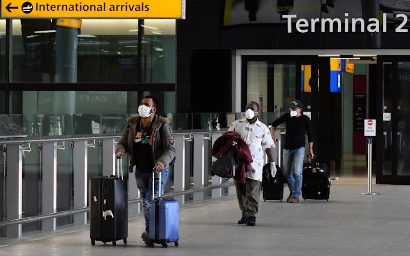 Passengers wearing PPE walk through the arrivals hall after landing at at Terminal Two of London Heathrow Airport - AFP