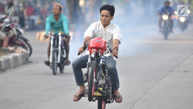 Seorang pembalap mengangkat sepeda motornya saat ikut dalam balapan liar di Jakarta, Minggu (27/5) pagi. Mereka memanfaatkan sepinya arus lalu lintas kendaraan untuk balapan liar. (Merdeka.com/Iqbal S Nugroho)