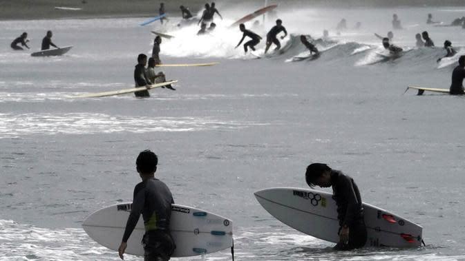Orang-orang berselancar di pantai Katase-kaigan yang berangin, Fujisawa, Prefektur Kanagawa, selatan Tokyo, Jepang, Kamis (24/9/2020). Badai Tropis Dolphin bergerak di sepanjang pantai Pasifik Jepang. (AP Photo/Eugene Hoshiko)