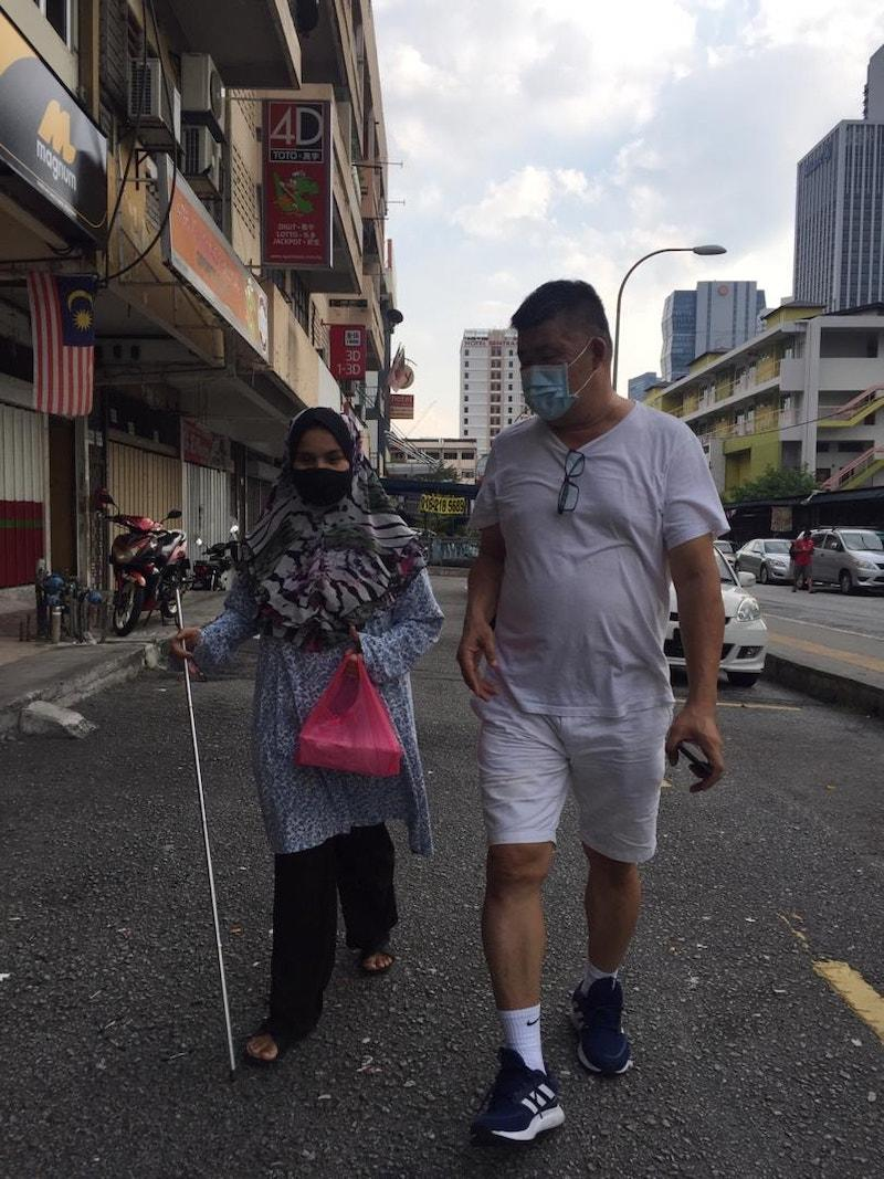 Uncle Kentang assisting a blind lady during one of his distribution runs. — Picture courtesy of Facebook/ Kuan Chee Heng