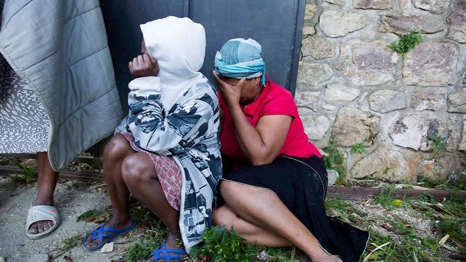Staf pekerja Panti Asuhan Church of Bible Understanding menangis di luar rumah anak-anak, pagi hari setelah kebakaran mematikan terjadi di fasilitas di Kenscoff, di pinggiran Port-au-Prince, menewaskan 13 anak-anak [Dieu Nalio Chery / AP Photo]