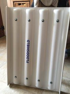 A sturdy, white board with 'floodshield' written on it stands in a living room.