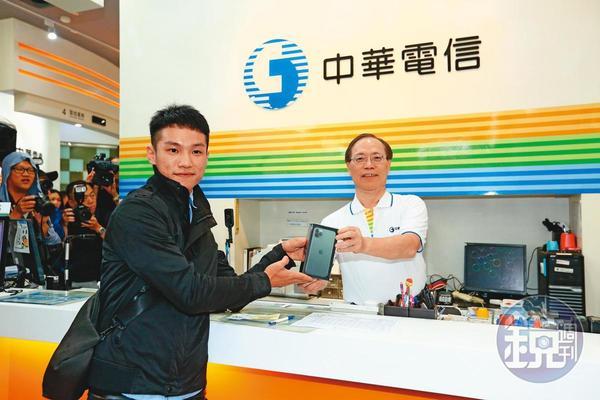 去年果粉排隊140小時,謝繼茂(右)化身1日店長,售出中華電信首支iPhone 11手機。