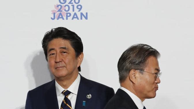 Presiden Korea Selatan (kiri) berjabat tangan dengan Perdana Menteri Jepang Shinzo Abe (kanan) di KTT G-20 tahun 2019 (AFP/Kim Kyung-Hoon)