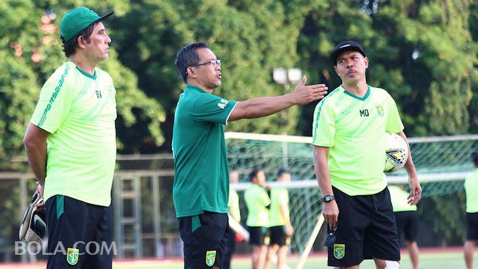 Mustaqim (kanan) berbincang dengan Aji Santoso (tengah) dalam sesi latihan Persebaya Surabaya. (Bola.com/Aditya Wany)