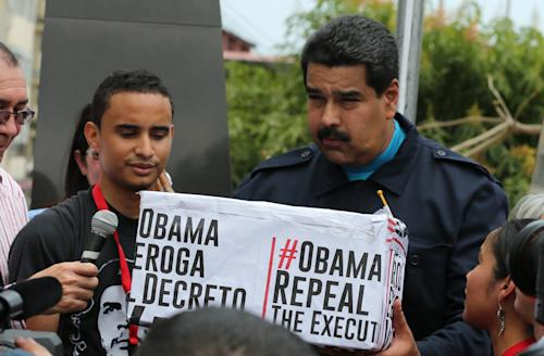 FILE - In this April 10, 2015 file photo, Venezuela's President Nicolas Maduro, right, holds a box covered by hastags that contains signatures from supporters who signed a petition asking the U.S. to end sanctions against Venezuela during a ceremony in the neighborhood of Chorrillo in Panama City. Maduro has become the third most-retweeted public figure in the world, behind Pope Francis and the King of Saudi Arabia, according to public relations firm Burston Marsteller. But a closer look suggests that the government is artificially inflating its social media pull by using networks of fake accounts. (AP Photo/Ramon Espinosa, File)
