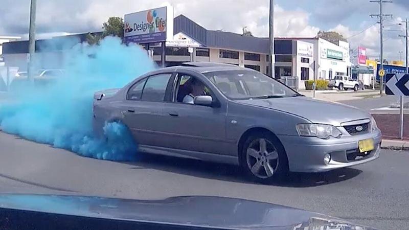 A driver of a Ford sedan is shown in dash cam footage filmed in Strathpine, near Brisbane, doing what appears to be a gender reveal burnout.