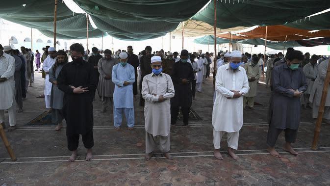 Umat muslim mengenakan masker saat melaksanakan salat Jumat berjemaah selama Ramadan di Masjid Jamia, Rawalpindi, Jumat (1/5/2020). Umat muslim dunia melewati Ramadan tahun ini di tengah pandemi COVID-19. (Aamir QURESHI/AFP)