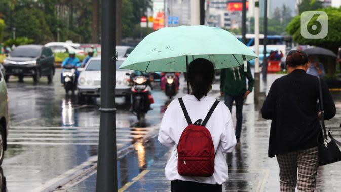 Warga menggunakan payung saat hujan mengguyur kawasan Jakarta, Senin (3/2/2020). Badan Meteorologi, Klimatologi, dan Geofisika (BMKG) merilis informasi peringatan dini cuaca ekstrem yang diperkirakan berlangsung hingga Rabu (5/2/2020) mendatang. (Liputan6.com/Angga Yuniar)