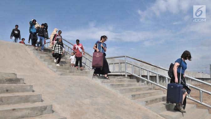 Wisatawan melintasi tangga tanggul laut yang telah selesai dibangun di Pelabuhan Kali Adem, Muara Angke, Jakarta, Selasa (12/2). Pembangunan tanggul laut tersebut memiliki tinggi 4 meter. (Merdeka.com/Iqbal S. Nugroho)