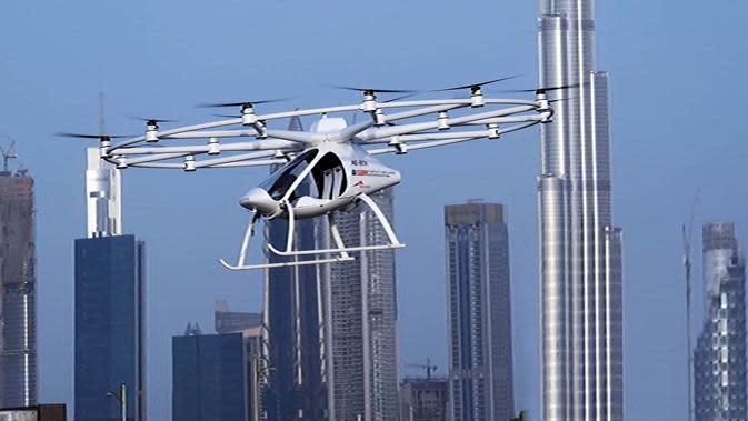 Sebuah drone yang akan dioperasikan sebagai taksi terbang dalam uji coba di Dubai, Senin (25/9). Mobil ini disebut bisa terbang dengan kecepatan 100 km/jam dan dengan kapasitas baterainya saat ini, mampu berada di udara selama 30 menit. (Handout/WAM/AFP)