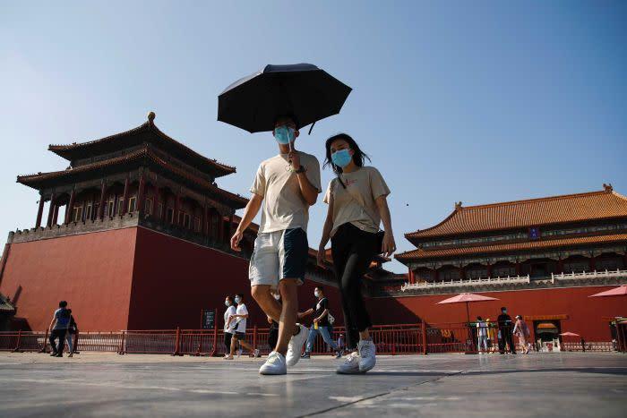 A couple wearing masks walking inside the Forbidden City in Beijing.